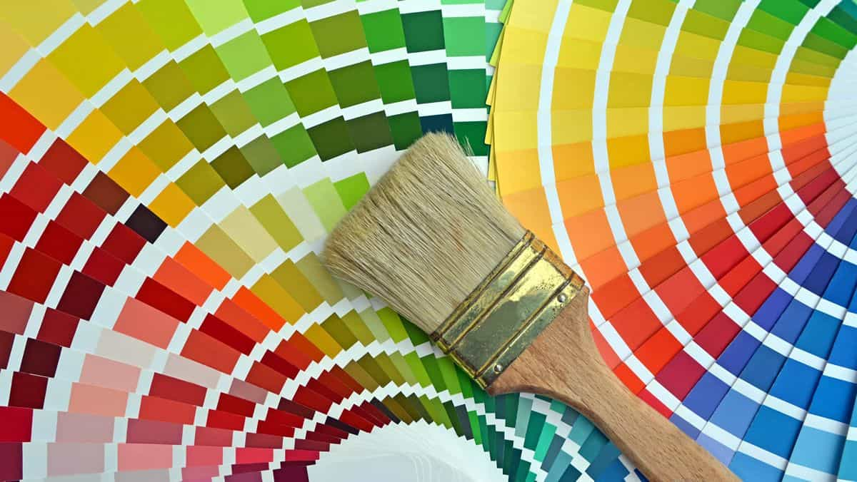 A number of color palettes, ranging from red to yellow to green to blue, fanned out with a paintbrush on top.
