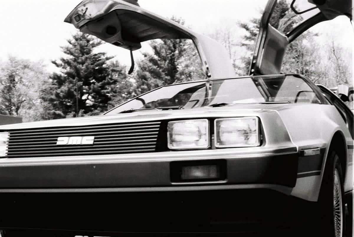 A black and white photo of the front of a DeLorean DMC-12, its characteristic gull-wing doors open.