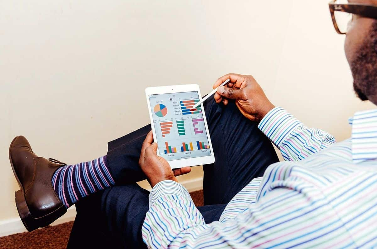 Back view of a businessman in a suit looking at a tablet screen with colorful graphs, the future of mobile app development lies in enterprise and not consumer apps.