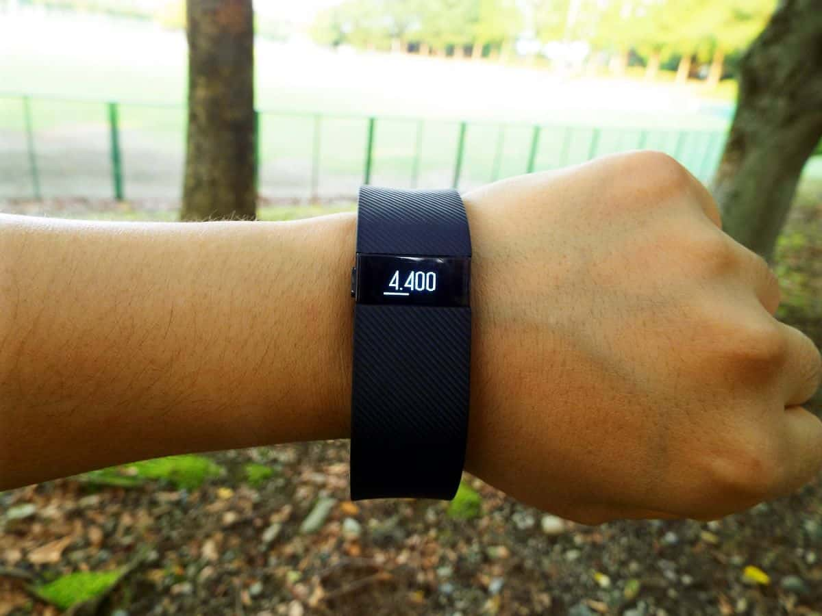 A close-up of a person's arm, a dark purple FitBit around the wrist displaying a step count of 4,400.