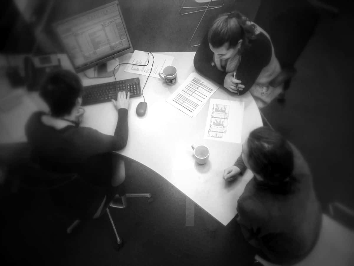 A top-down view of a mobile UI design team of three people sitting at a desk with cups of coffee, notes and a desktop computer, discussing budget and scope of a project.