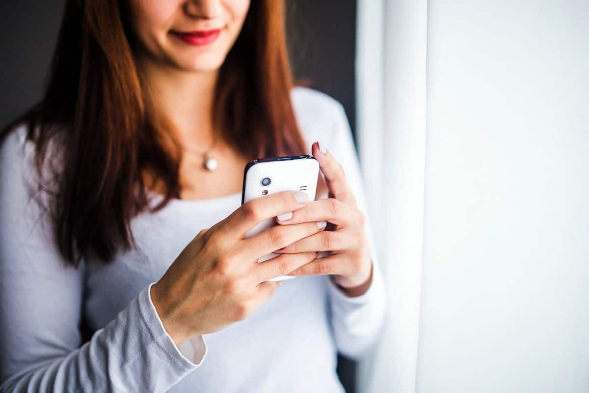 A young woman smiling while looking at mobile phone, which is the kind of reaction guerrilla UXers should aim for