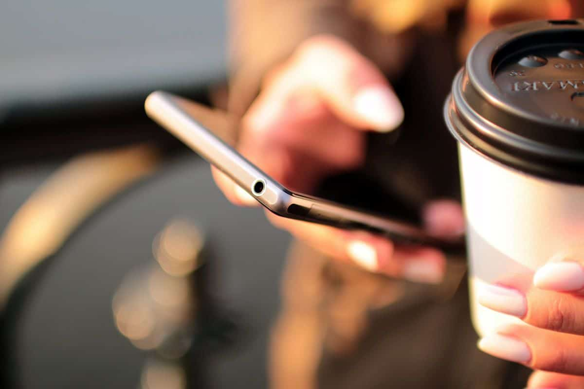 A close-up of a woman's hand holding a smartphone, a cup of coffee in her other hand.