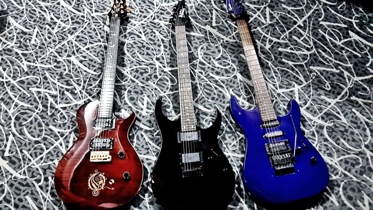 A red Opeth Signature PRS, a black Ibanez, and a blue Squire electric guitar lie next to each other in a row.