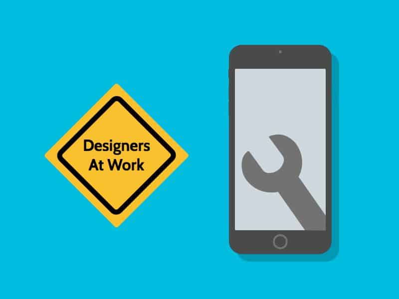 Mobile phone with wrench icon on screen and a keep out sign that says designers at work.