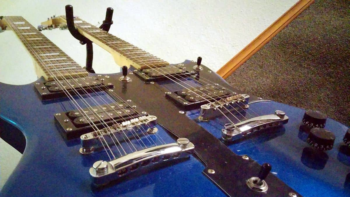 A bottom-up view of a blue double-neck guitar, one neck with six strings and the other with 12.