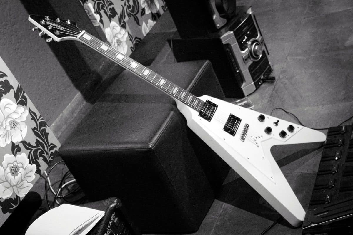 A black-and-white photo of a white Gibson Flying V guitar leaning against an ottoman.