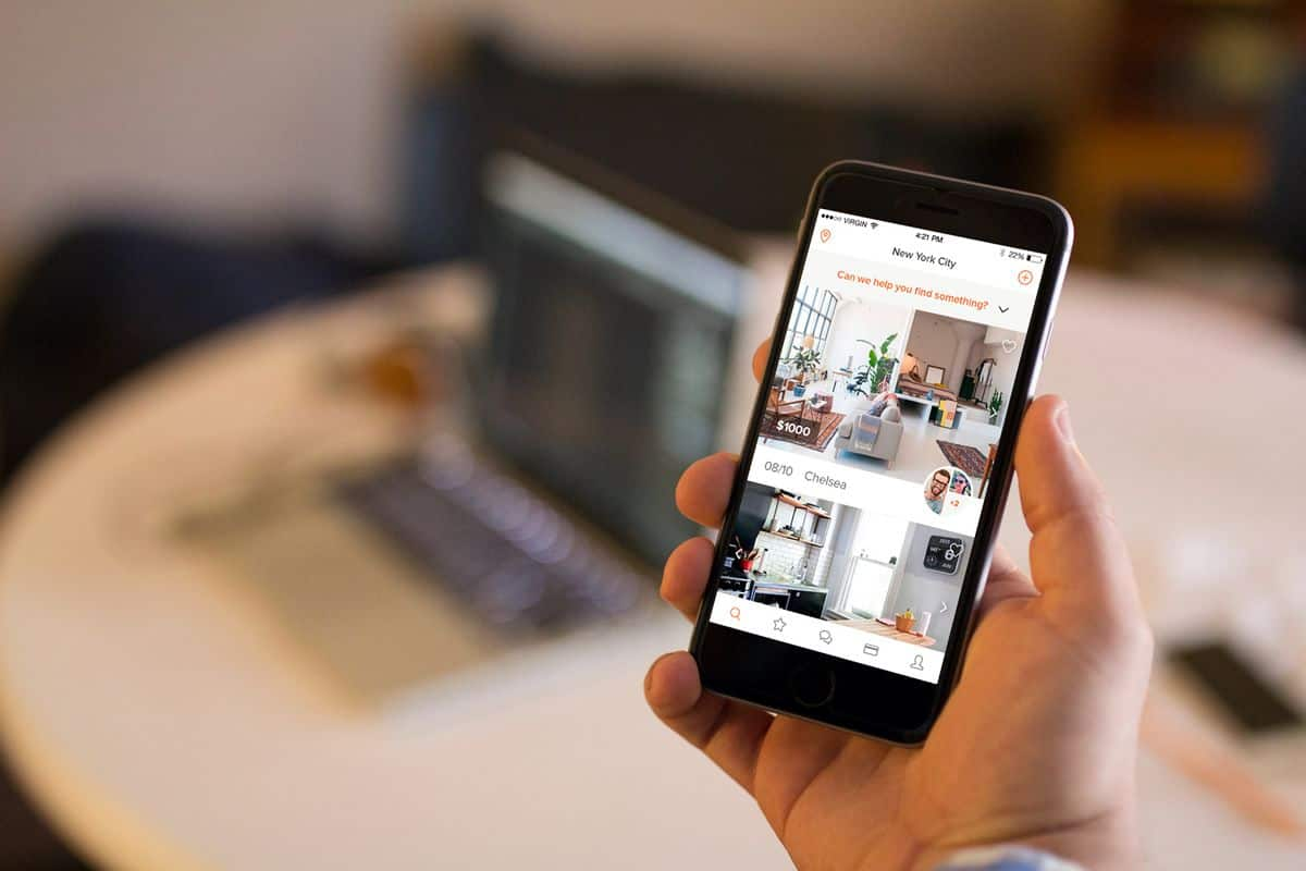 An iPhone displays a screenshot with a picture of a potential apartment on the Roomi iOS app.