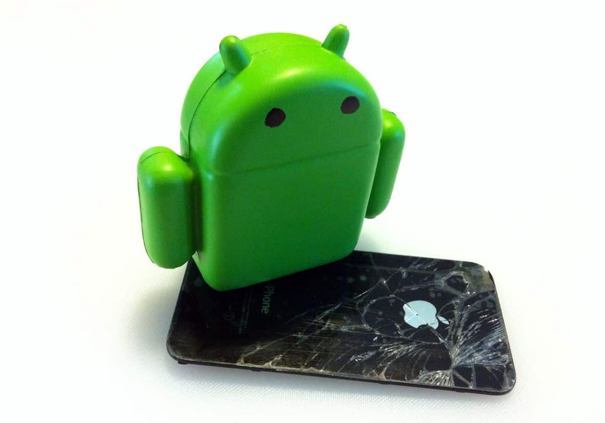 A figurine of the Android mascot stands on top of an iPhone with shattered glass.