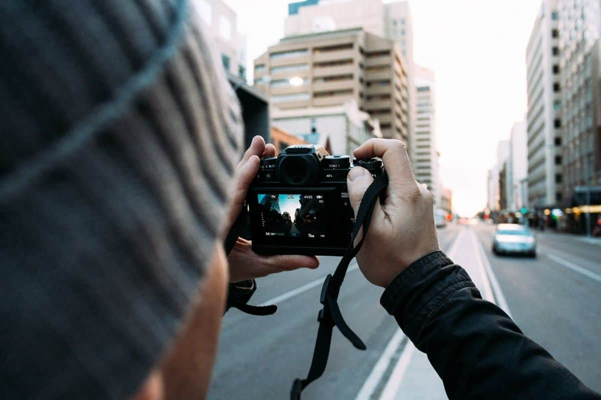 A man taking photo in the middle of the street, photography can be a great way to gain design inspiration.