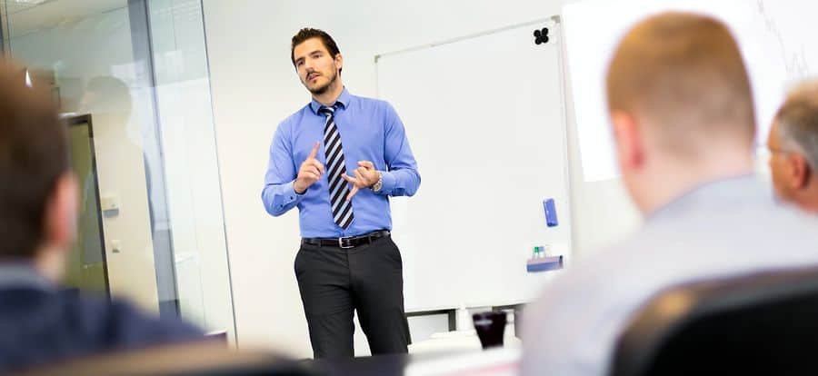 A young male project manager stands in front of a whiteboard, presenting at a team meeting.