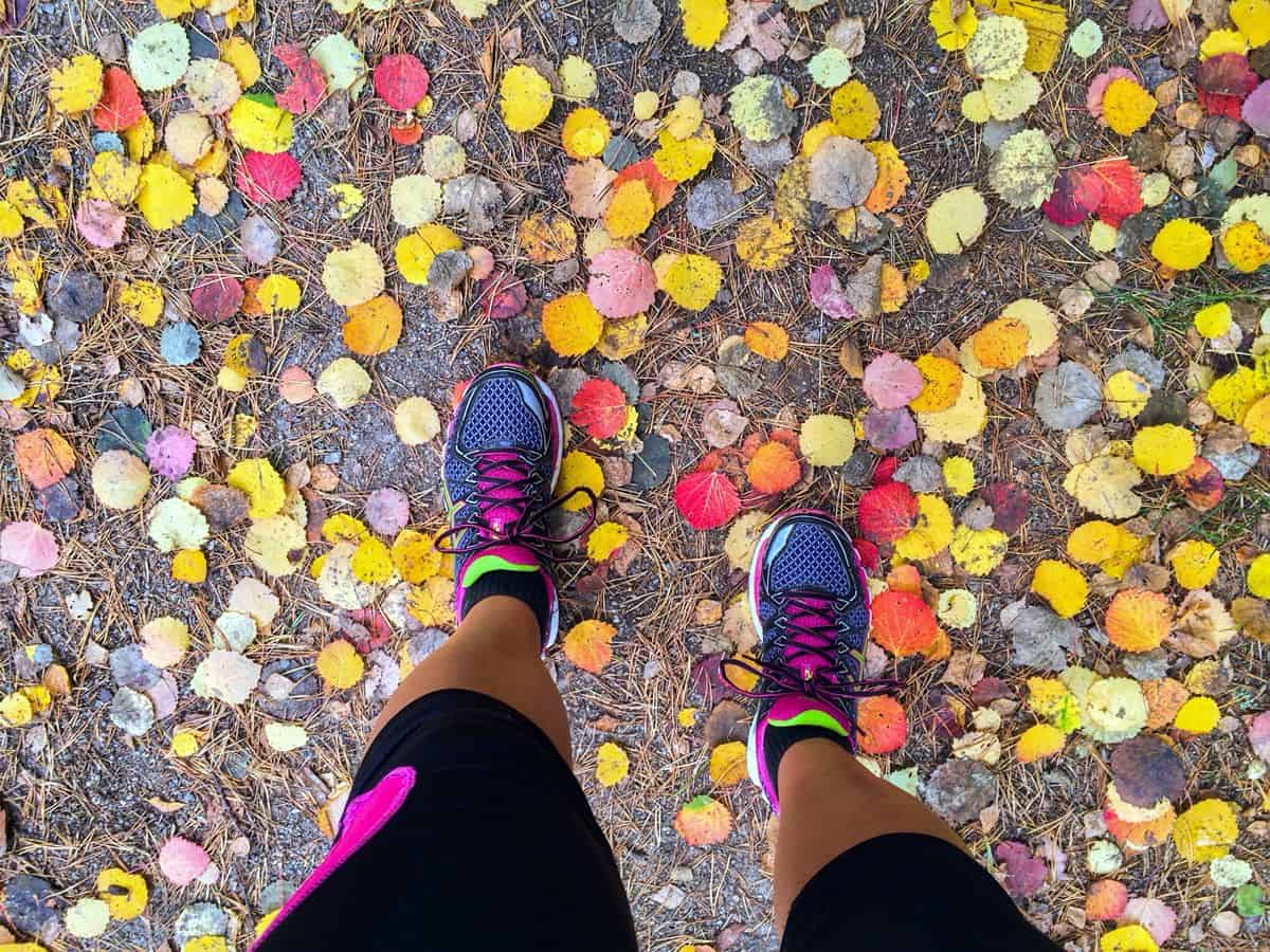 A top-down view of a woman wearing brightly colored running sneakers on a fall day, with leaves on the ground around her.