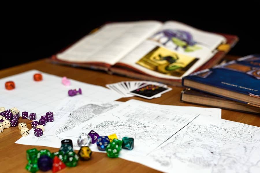 Maps, cards, open books, and multi-sided dice on the table of a tabletop RPG player. What if we could combine the magic of RPGs with the world of fitness apps?