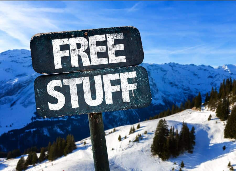 """A frosty sign says """"Free Stuff"""" against a snowy mountain backdrop."""