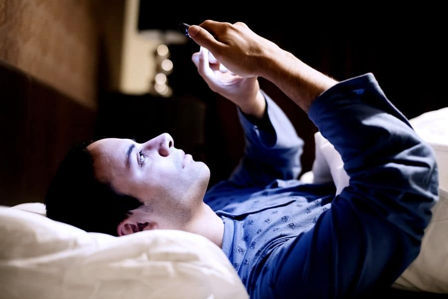 A photo of a man lying in bed in a darkened room, playing a game on his mobile phone.