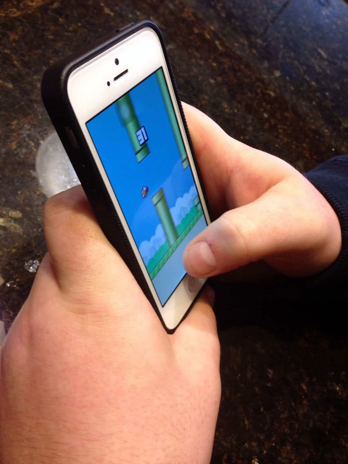 A close-up of a person playing Flappy Bird, a game as challenging as it is addictive, on an iPhone.