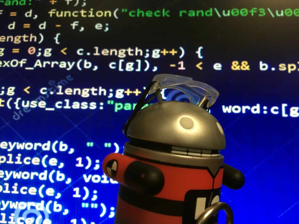 A metal Android figurine in front of a screen of mobile app code.