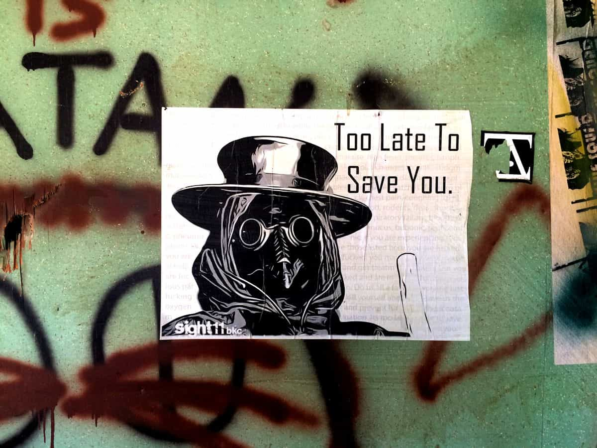 """A black and white piece of art featuring a bird with goggles, a top hat and a hood, with the caption """"Too Late to Save You,"""" stuck to a wall with spraypainted graffiti."""