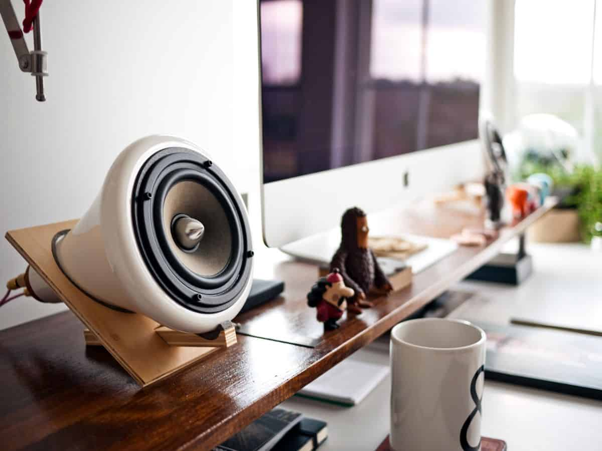 A close-up photograph of a set of audio speakers connected to an Apple iMac display on a designer desk setting.