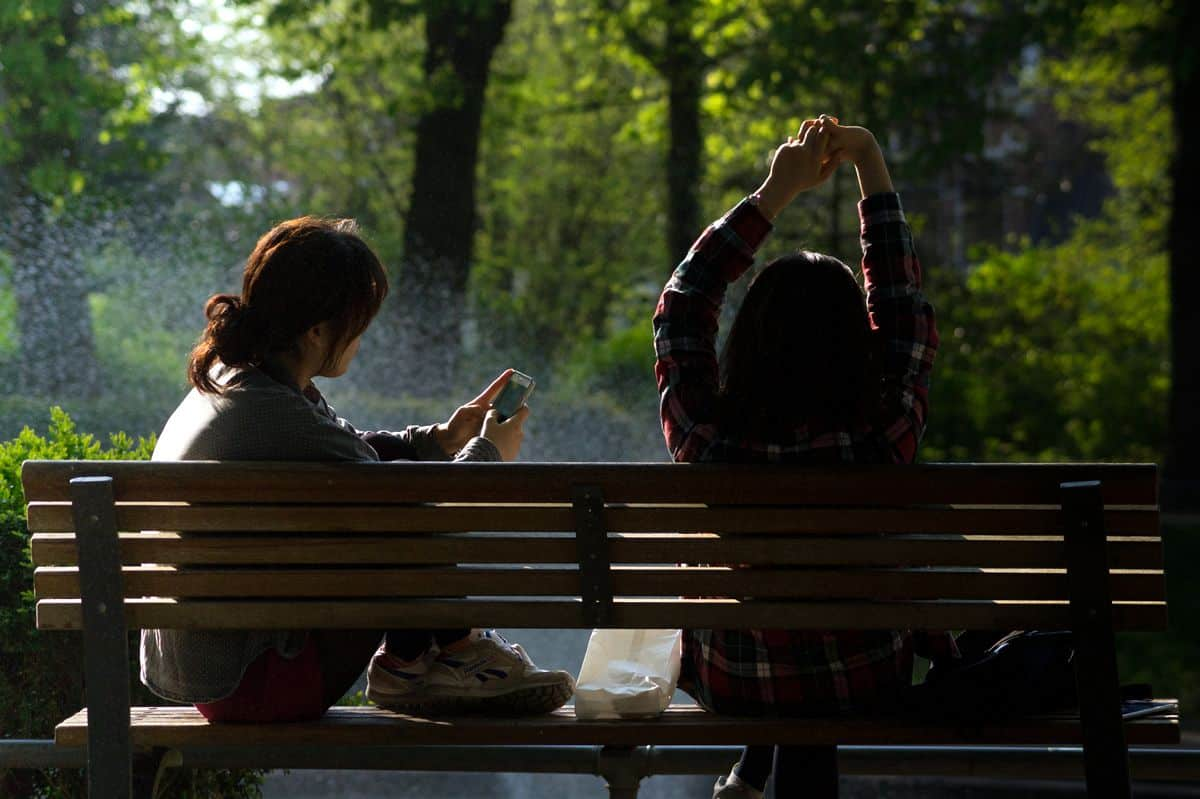 Two women sitting on a park bench, the one on the left using her mobile phone and the other stretching her arms overhead.