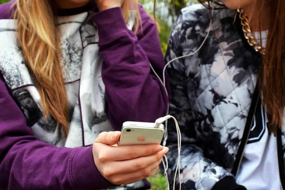 Two young women sitting next to each other sharing a pair of earphones connected to an iPhone.