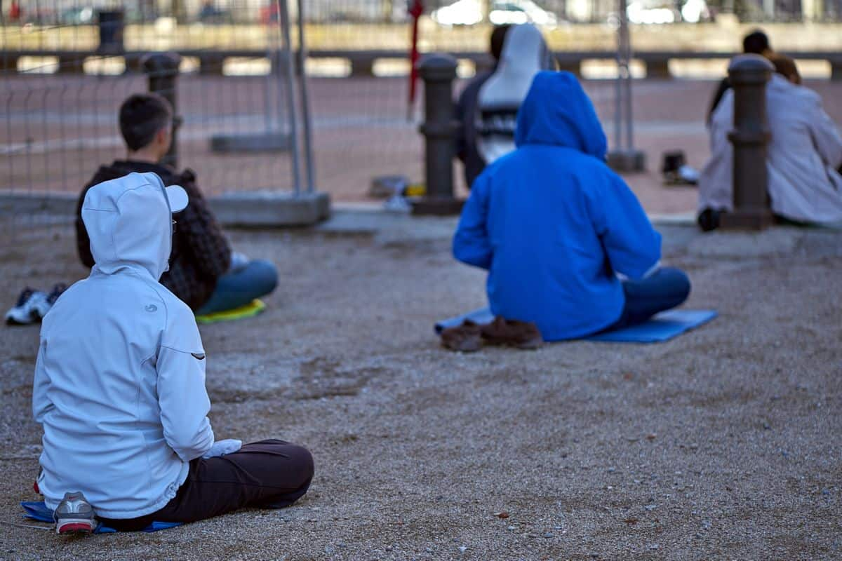 A number of students sit cross-legged in a park, practicing mindfulness meditation.