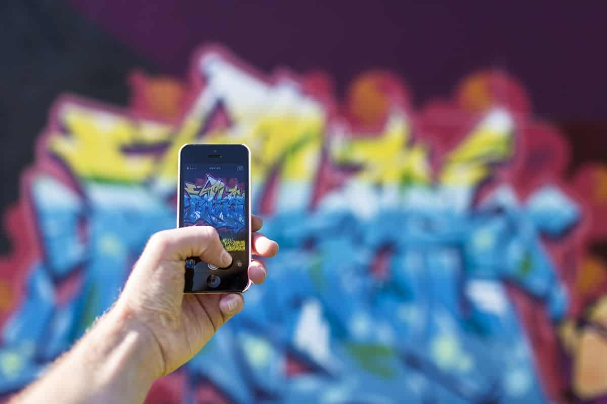 A close up of the hand of a young man holding a mobile phone and taking a picture of a blurred graffiti backdrop which is captured clearly on the screen.