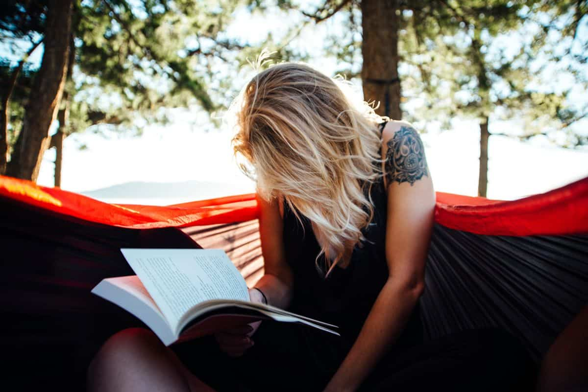 A young woman sitting in a hammock burying her head in a book.