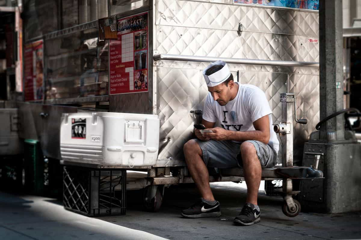 A young man wearing a cook's hat sitting next to a food truck in New York, comfortably busy on his mobile phone.