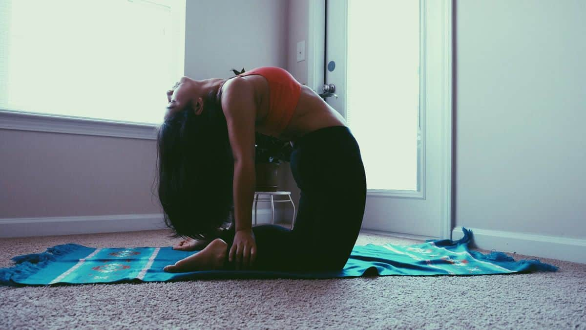 A woman in camel pose practices yoga in her own home, a possibility made easier by visual designers creating apps for personal fitness.