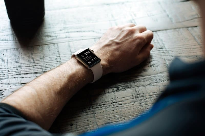 Close up image of the Apple Watch white band on a male user's arm resting on a wooden table.