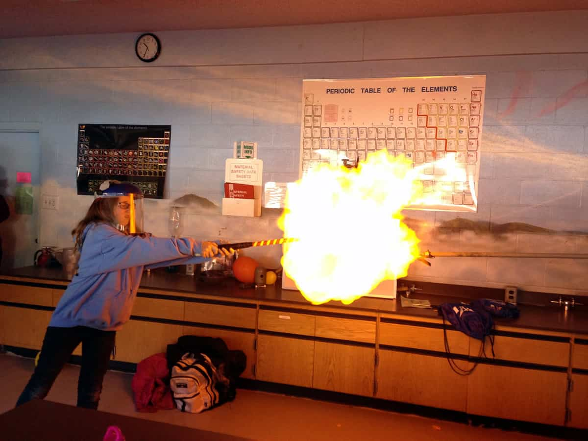 A chemistry major wearing ample safety gear creates a makeshift blowtorch in a college classroom.