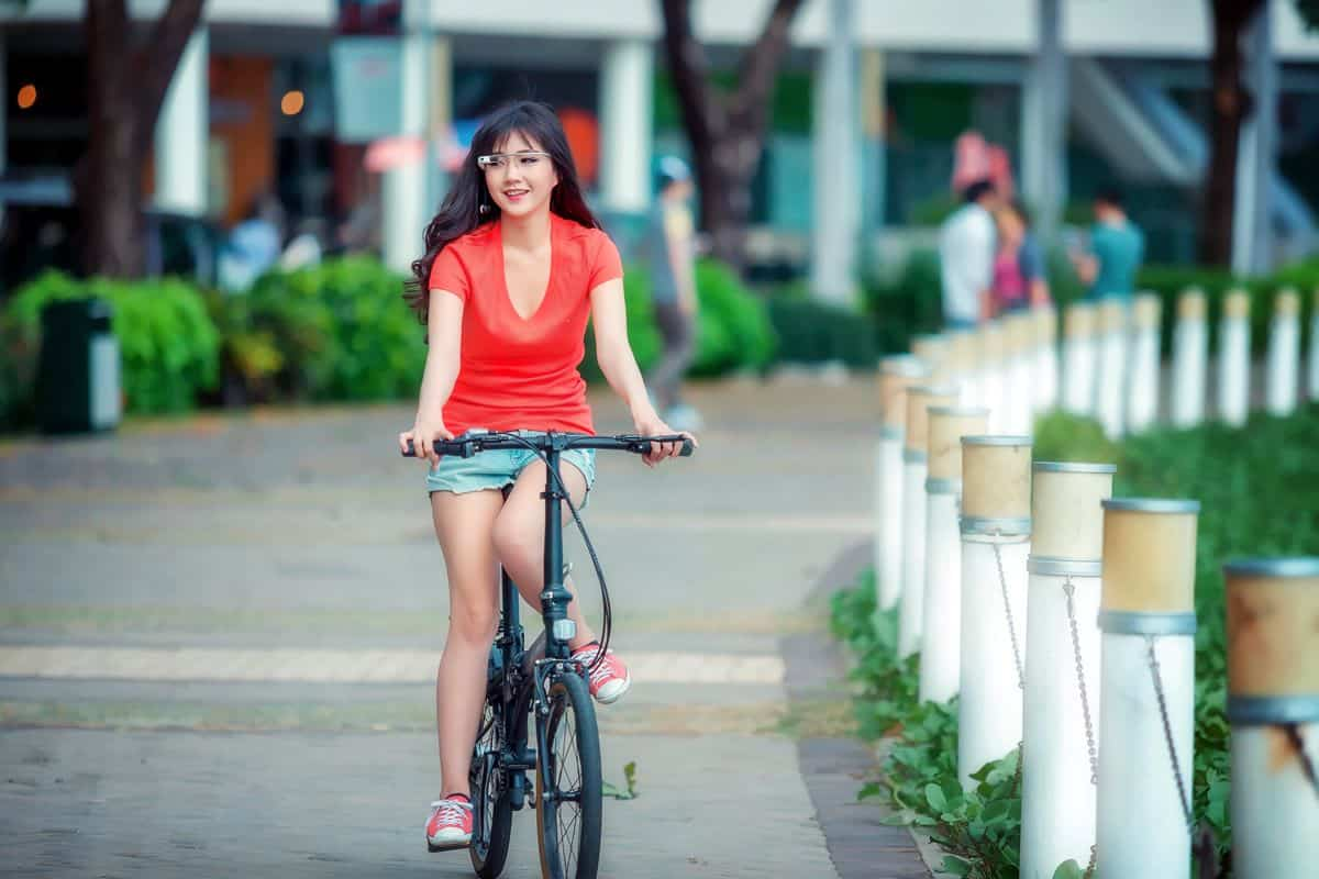 A woman in a red shirt rides her bike through a city park while wearing Google Glass, the company's foray into augmented reality.