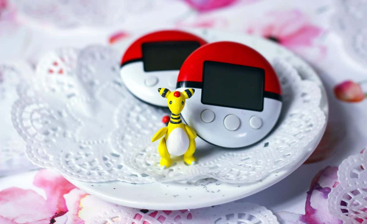 A small Pokemon figurine stands on a small tea dish on top of delicate doilies, in front of two PokeWalkers.