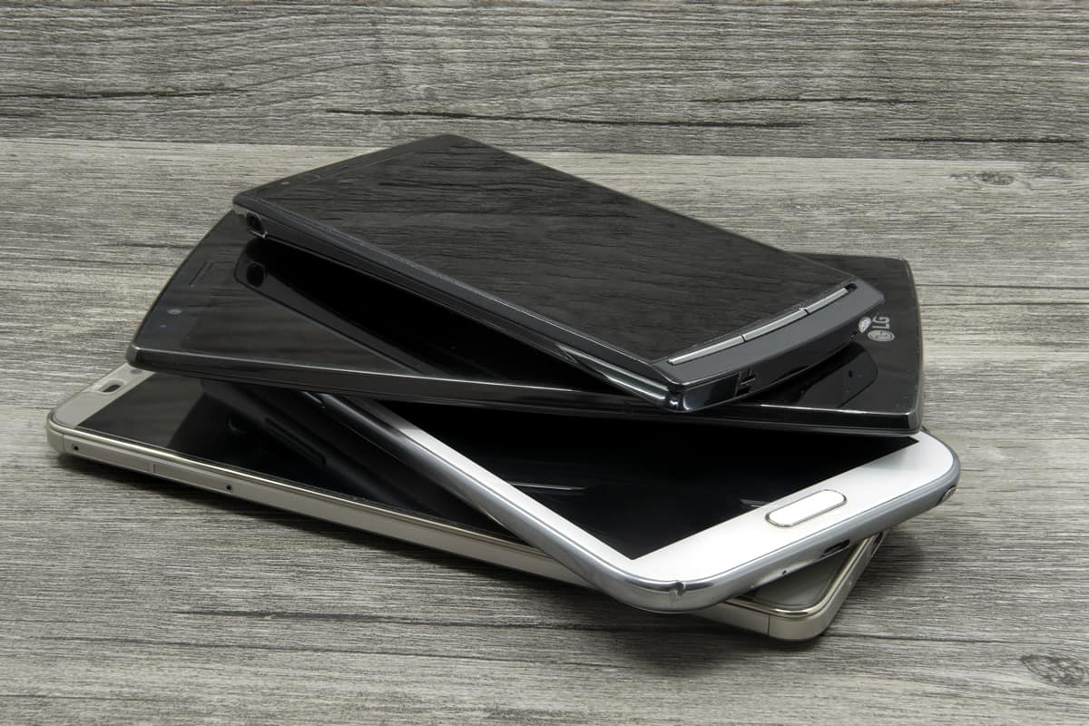 A stack of mobile devices — some old, some new — sits on a grey wooden table, awaiting mobile usability testing.