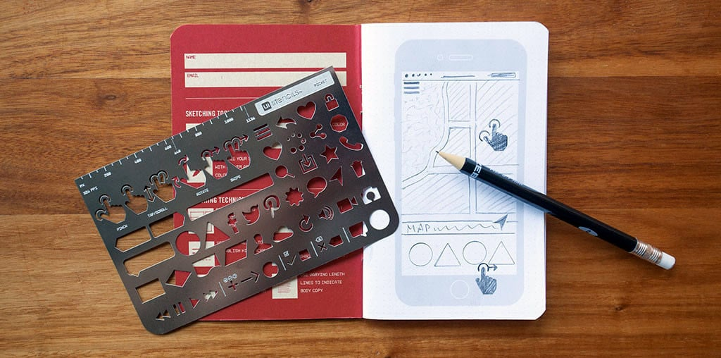 Everyday Carry Kit in action: a mobile app UI sketched out on the notebook using the included stencil and pencil.