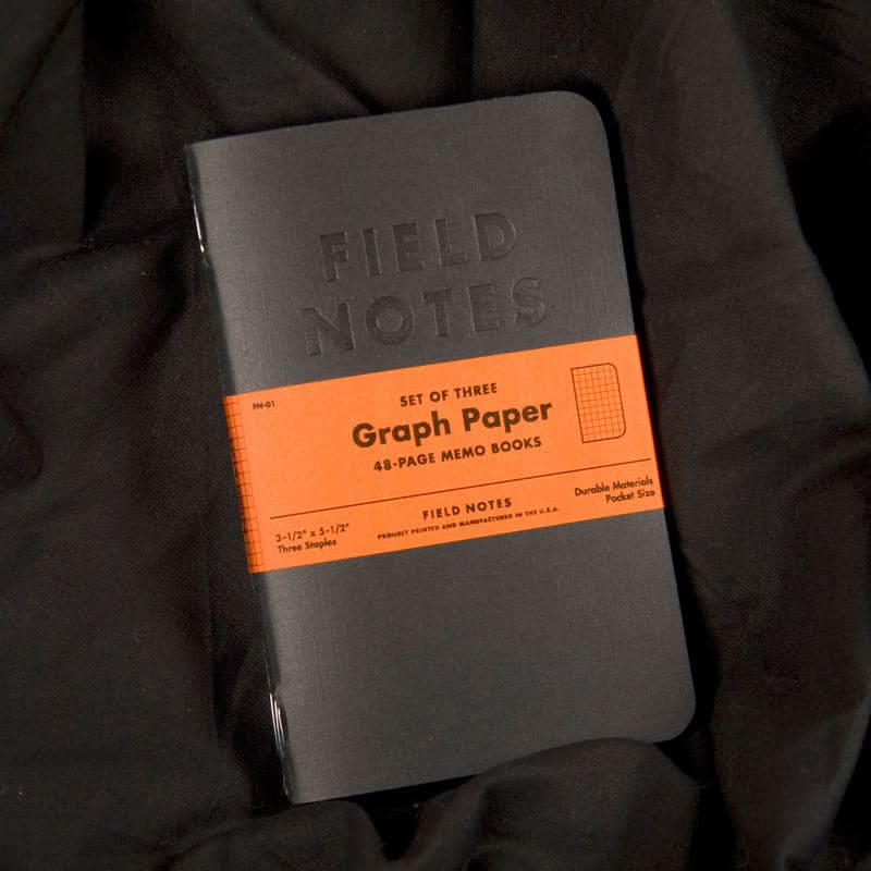 Field Notes notebooks for designers in black, placed on folded black fabric background.