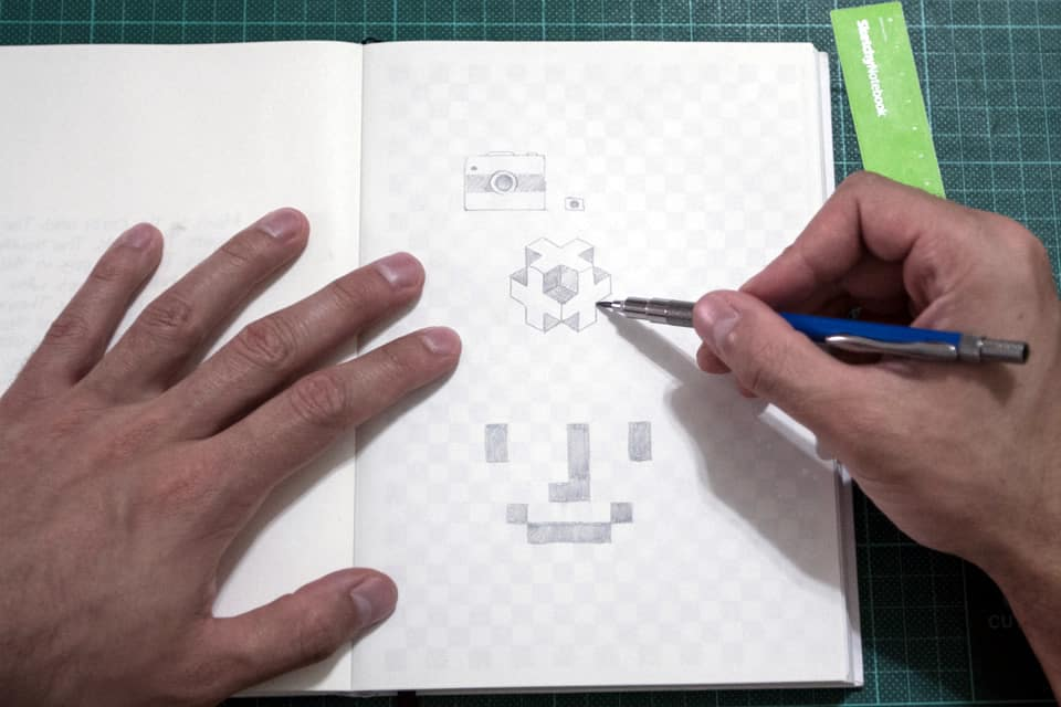 Person drawing cubes with a pen a page of a SketchyNotebook.