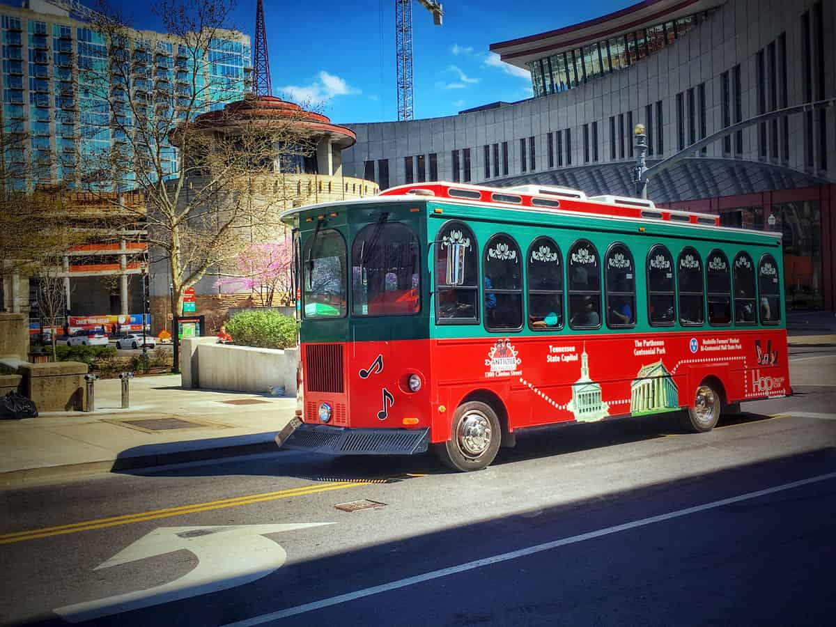 A red and green trolley drives through a peaceful city street.