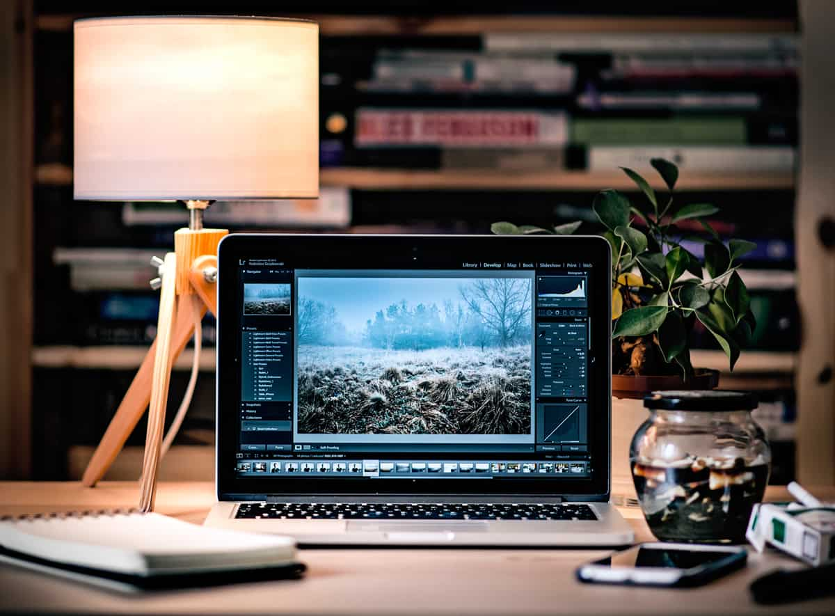 A MacBook opened to a photo editing software on a work desk with a book shelf in the background.