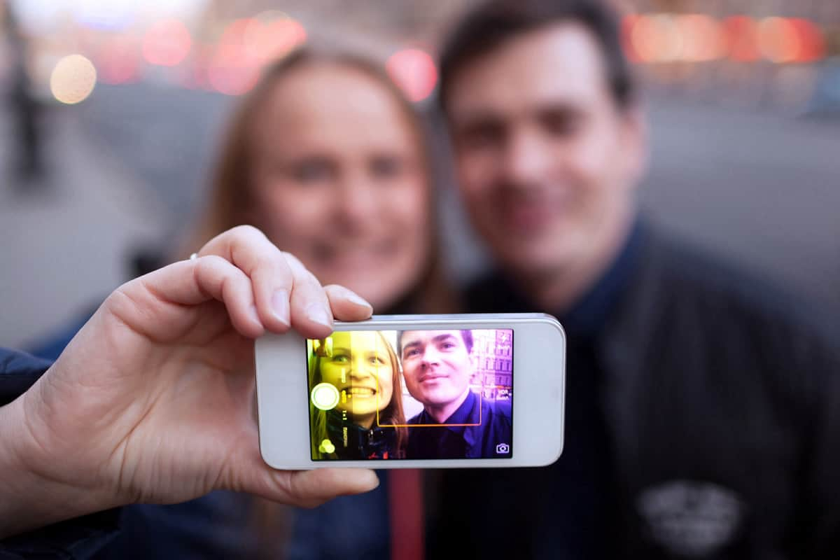 A photo of a couple taking a selfie using the Instagram app on an iPhone.