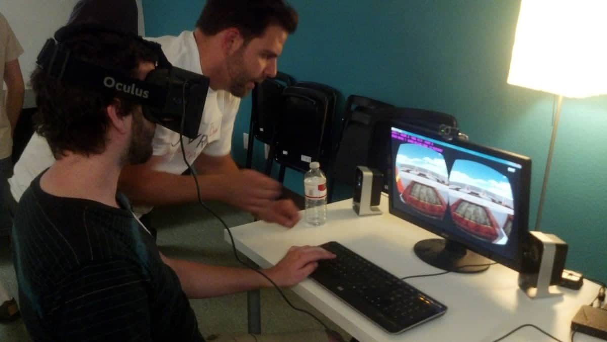 A photo of a man using an Oculus Rift virtual reality headset while his friend looks on.