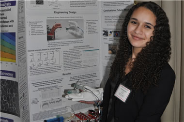 A photo of Simone Braunstein standing in front of a poster board detailing her research.