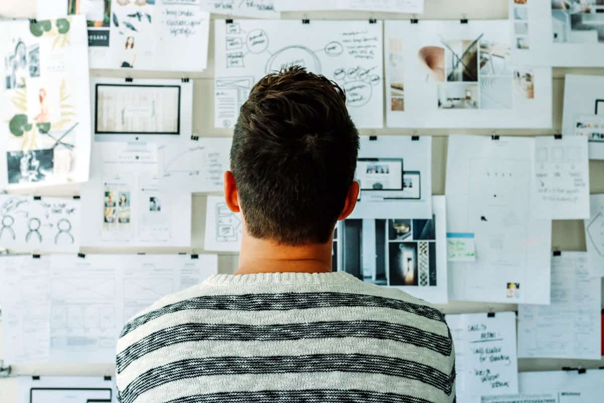 A photo of a man looking at a wall full of design ideas.