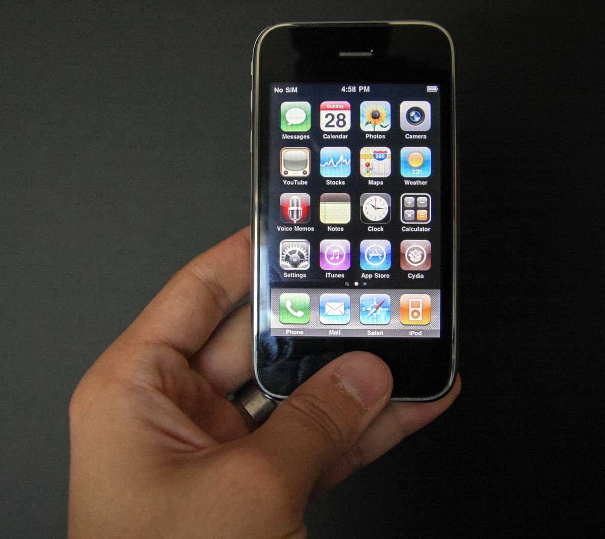 An image of an iPhone 3G in a man's hand.
