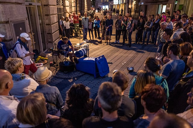 A photo of a crowd gathering to watch a street performer use unique pieces as a drum set.
