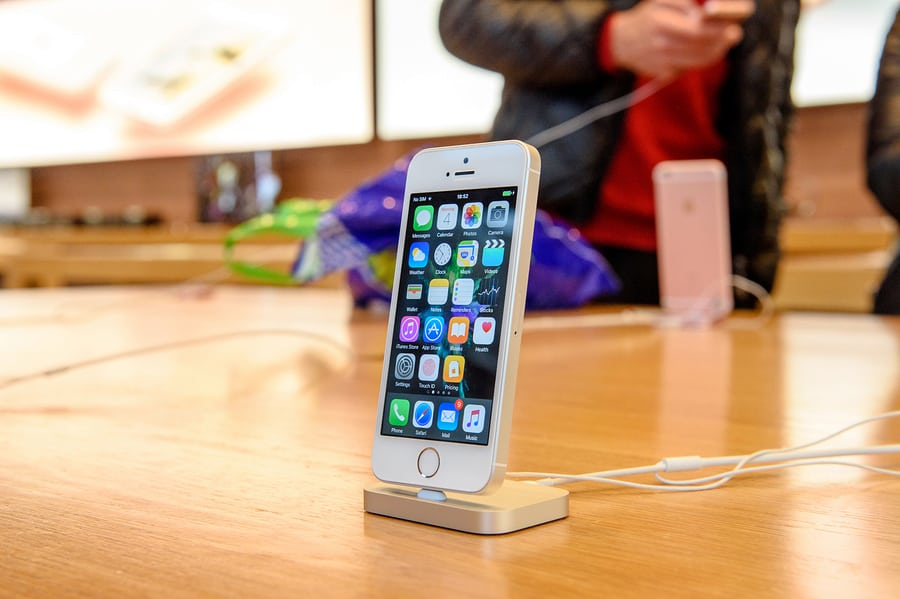 A photo of an iPhone SE in a docking station at an Apple Store.
