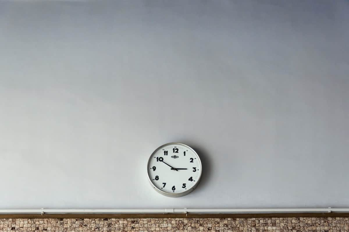Image of a clock on a bare gray wall.
