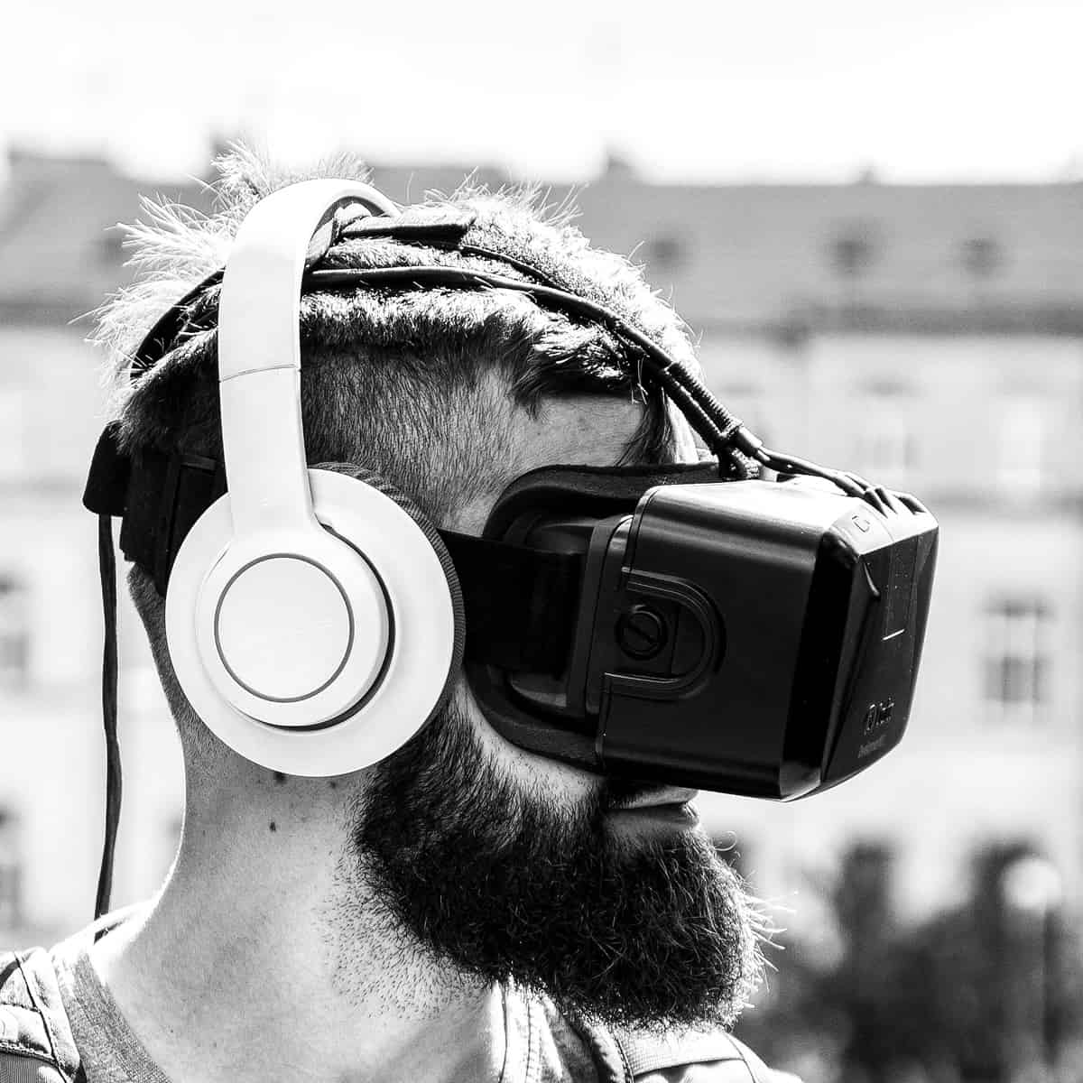 A photo of a man wearing headphones and a virtual reality head-mounted display.