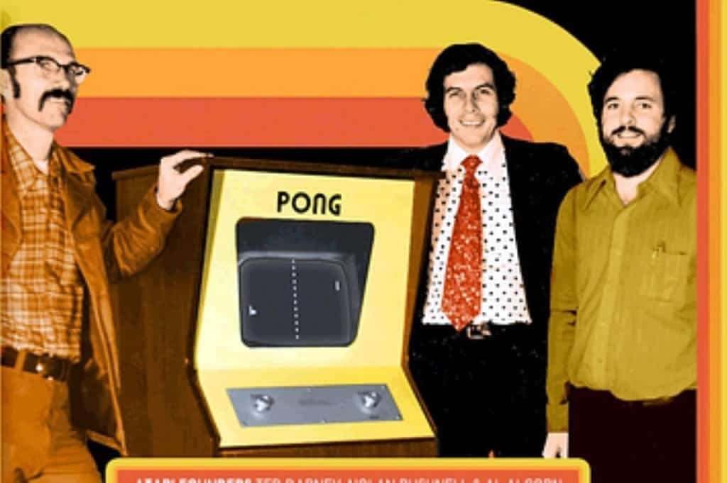 A photo of the creators of Pong next to a Pong game cabinet.